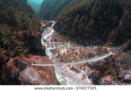 Suspension bridge on abyss of mountain river, modern trekking path, active sport adventure, travel in Himalaya, dangerous place on trek near Everest Base Camp, Himalayan mountain, Sagarmatha, Nepal - stock photo