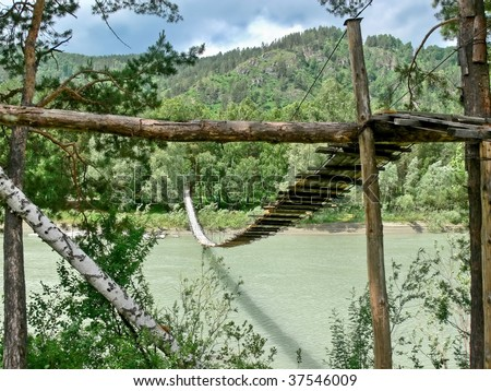 Suspension bridge over river Katun in mountains - stock photo