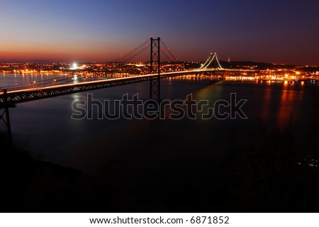 Suspension Bridge over the Tagus River, in Lisbon at dusk - stock photo