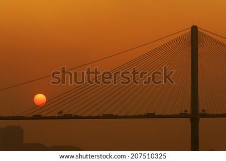 Suspension bridge silhouette at sunset  - stock photo