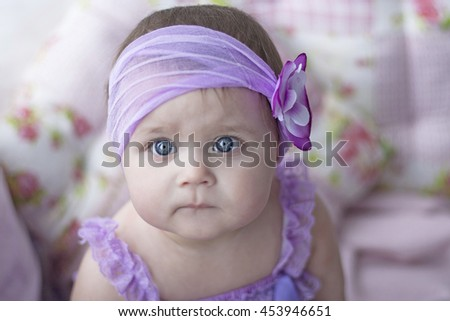 suspicious baby girl in lavender dress with flower headband at interior with lavender