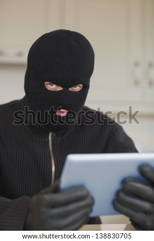 Suspicious burgler holding tablet pc in kitchen - stock photo