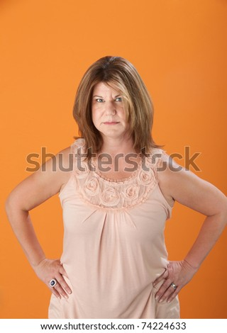 Suspicious Caucasian blonde woman on orange background - stock photo
