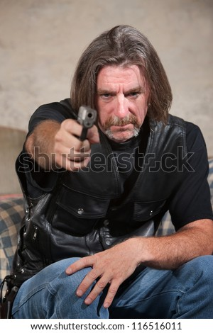 Suspicious male in biker gang clothing aiming a pistol