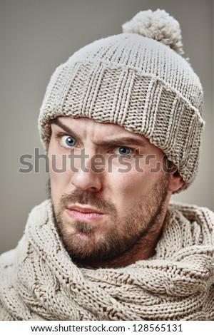 Suspicious Man Wearing Warm Winter Clothes In Studio