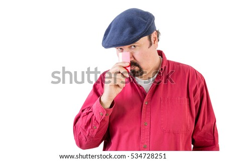 Suspicious middle-aged man wearing a cloth cap peering over his credit card with a speculative watchful expression as he holds it to his nose