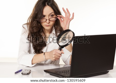 suspicious secretary in white shirt did found something on her laptop with a magnifying glass - stock photo