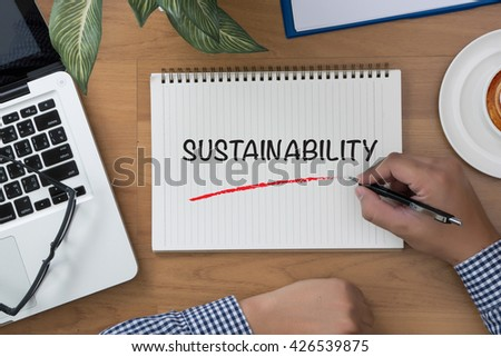 SUSTAINABILITY man hand notebook and other office equipment such as computer keyboard - stock photo