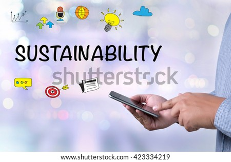SUSTAINABILITY person holding a smartphone on blurred cityscape background - stock photo