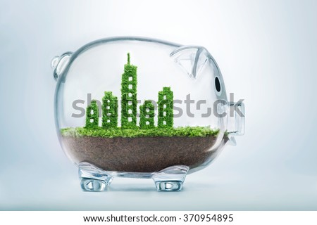 Sustainable urban development concept with grass growing in shape of a city inside transparent piggy bank