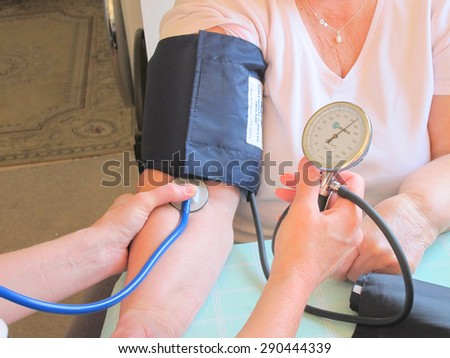 SUTTON-IN-ASHFIELD, NOTTINGHAMSHIRE, UK. JUNE 24, 2015. A care nurse taking a stroke patient's blood pressure at home at Sutton-in-Ashfield in Nottinghamshire, UK.