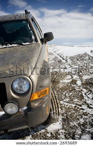 SUV in need of a wash after straying off the beaten path. Closeup with focus on front of vehicle. - stock photo