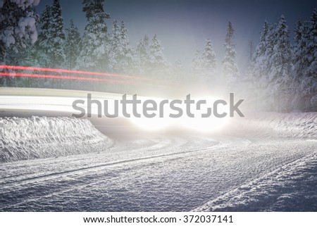 SUV light trails on a snowy winding road in Lapland, nothern Finland. Long exposure photo taken in the dusk. - stock photo