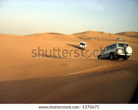SUVs Trek Across the Desert Dunes - stock photo