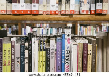 Suwon, Korea - July 20, 2016 : Books on a wooden shelfs in library - stock photo