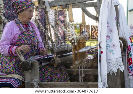 SUZDAL, RUSSIA - AUGUST 08, 2015: Russian woman weaves a carpet on vintage  loom during clebrate the City day in Suzdal on 8 of August 2015, Russia - stock photo