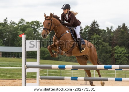 "SVEBOHOV, CZECH REPUBLIC - MAY 23: Closeup view of young blonde horsewoman jumping over an obstacle at ""Summer Jumping Event  2015"" on May 23, 2015  in Svebohov, Czech Republic."