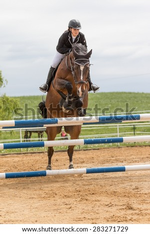 "SVEBOHOV, CZECH REPUBLIC - MAY 23: Front view of horsewoman in the first phase of the horses jump over a hurdle at ""Summer Jumping Event  2015"" on May 23, 2015  in Svebohov, Czech Republic."