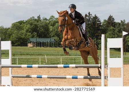 "SVEBOHOV, CZECH REPUBLIC - MAY 23: Young horsewoman is jumping over the hurdle at ""Summer Jumping Event  2015"" on May 23, 2015  in Svebohov, Czech Republic."