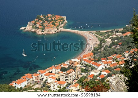 Sveti Stefan (Saint Stephen) is a seaside luxury resort in Montenegro. The resort on its peninsula with the causeway connecting to the surrounding beaches and the blue water of the Adriatic Sea. - stock photo
