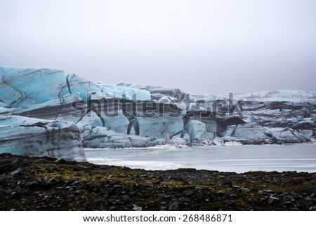 Svinafellsjokull blue glacier inches close to its final destination entering the glacier lagoon before it melts into the sea. - stock photo