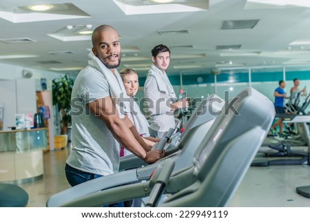 Svomestnye sports in the gym. Three young men running on a treadmill - stock photo