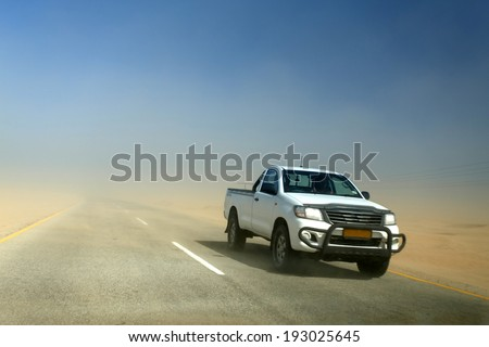 SWAKOMPUND, NAMIBIA - OCTOBER 31 2013: In a year of drought 4x4 vehicle drives through a sand storm through the Namib desert at Swakompmund, Namibia, Africa - stock photo