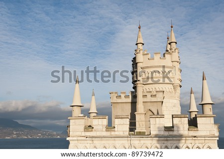 Swallow's Nest Castle tower, Crimea, Ukraine, with blue sky and Yalta town on background - stock photo