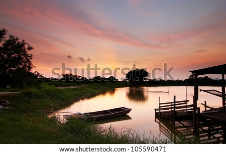 Swamp sunset with boat and house