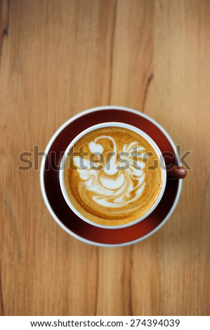 Swan drawing on latte art coffee cup - stock photo