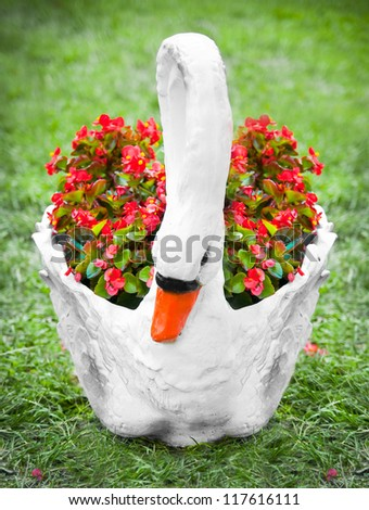 swan flower pot on the grass with flowers - stock photo