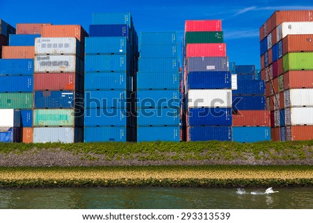 Swan taking off against containers stacked in Port of Rotterdam - stock photo