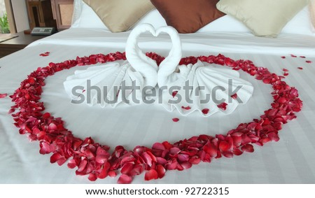 Swans made from towels surround by  red rose petals that make heart form - stock photo