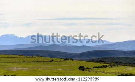 Swartberg Mountains in Southern Cape South Africa with some rare snow on it and green fields in the foreground - stock photo