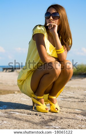 Swarthy young girl poses on the beach - stock photo