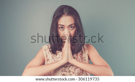 Swasdee with bad attitude. Vintage, retro style of portrait of Asian woman in pink vintage dress on blue - green background. - stock photo