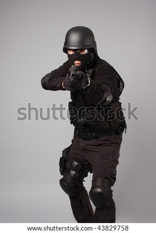 SWAT police officer aiming a shotgun. - stock photo