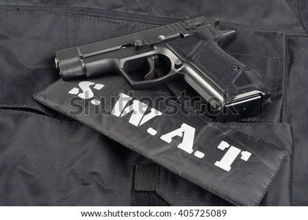SWAT teams concept -handgun on black uniform background  - stock photo