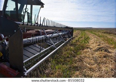 Swather in a prairie grain field at harvest time. - stock photo