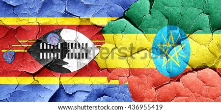 Swaziland flag with Ethiopia flag on a grunge cracked wall - stock photo