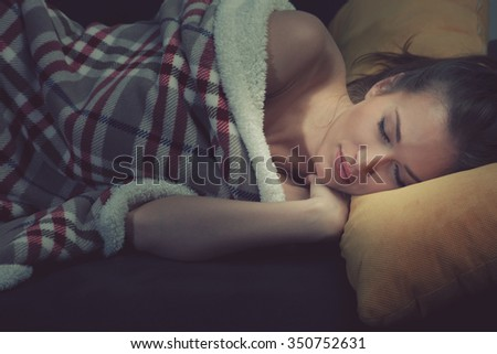 sweat dreams, young woman sleeping covered with warm blanket - stock photo