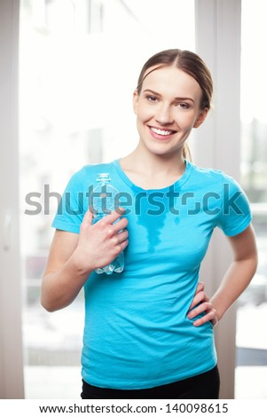 sweat women after workout holding bottle of water