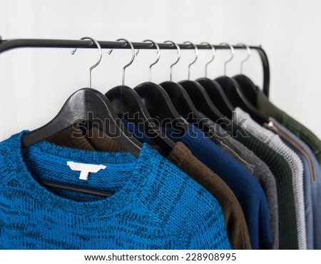 Sweaters Hanging on Metal Clothes Rack - stock photo