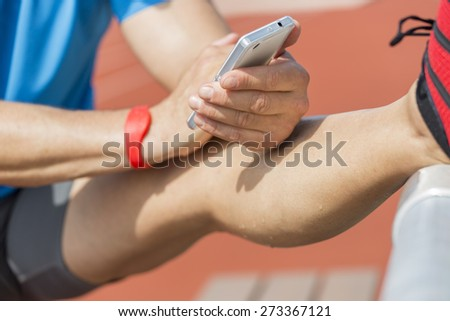 Sweating athlete is stretching after training and checks his fitness results on his smart phone. He wears a fitness tracker wristband on his right arm. - stock photo