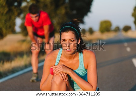 Sweaty athletes taking a rest after road running race or marathon. Tired female runner and man resting and breathing. Sport motivation and lifestyle concept. - stock photo