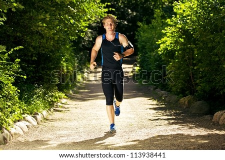 Sweaty man jogging while listening to music - stock photo