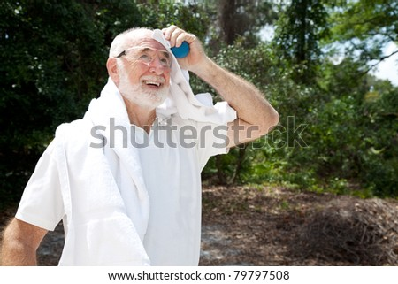 Sweaty senior man holding a racquetball and wearing safety glasses, dries himself with a towel. - stock photo
