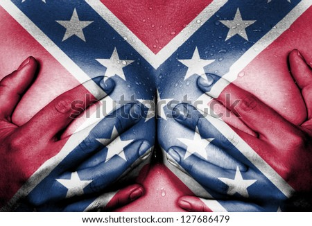 Sweaty upper part of female body, hands covering breasts, confederate flag - stock photo