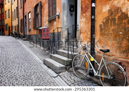 Sweden quaint cobblestone street in picturesque Gamla Stan, Stockholm's oldest neighborhood. Parked bicycles lean against the colorful plaster buildings. Biking is a popular way to get around town. - stock photo