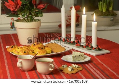 Swedish advent celebration Lucia buns and ginger bread on plate, blue cheese and mulled wine or glogg. Focus on plate
